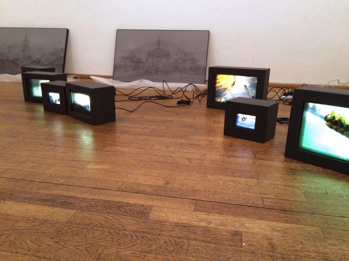 Aufbau der Ausstellung INBETWEEN, mehrere Tempografie und und Bilder stehen auf dem Boden