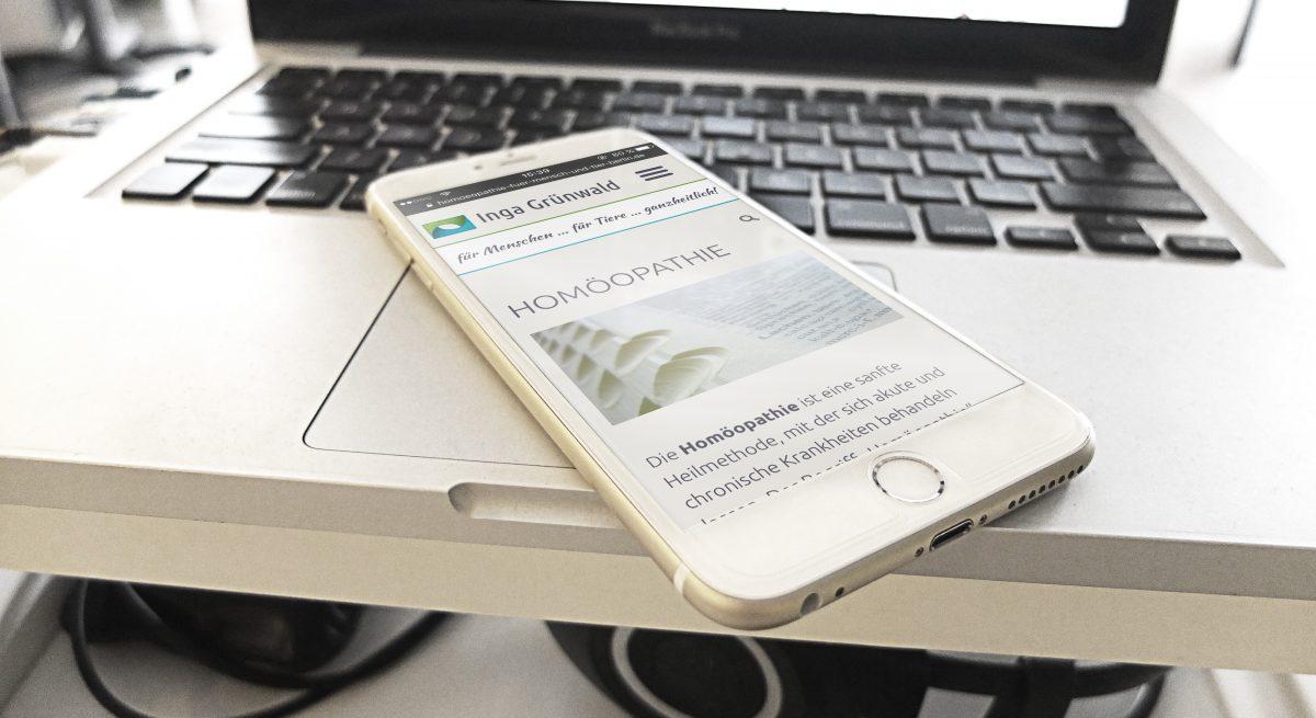 Die Webseite von Inga Grünwald in responsiver Ansicht auf einem Smartphone, das auf einem Computer liegt