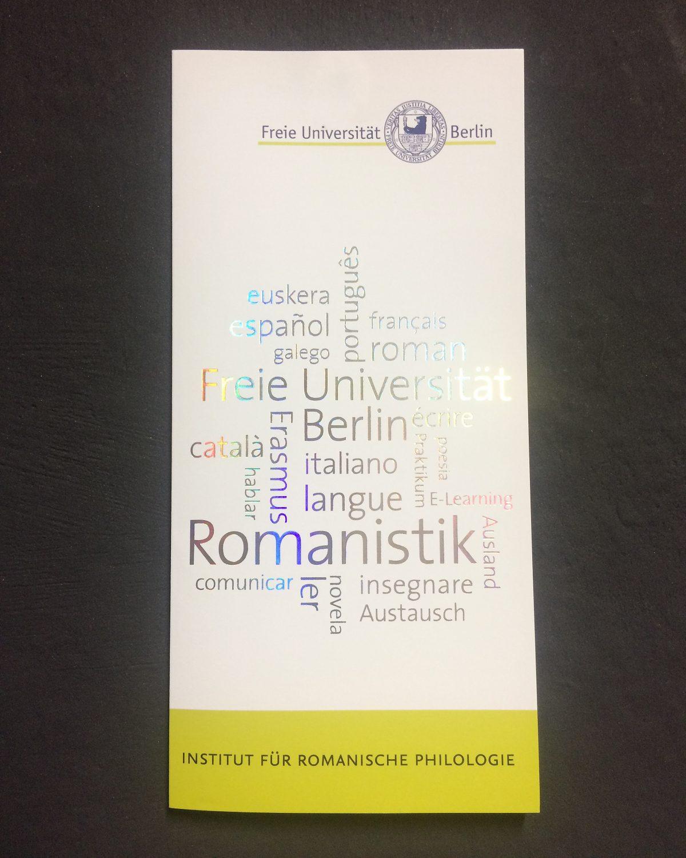 Vorderseite des Infofolders mit einer Wordcloud in Heißfolienprägung mit Laserfolie für das Institut für Romanische Philologie der Freien Universität Berlin