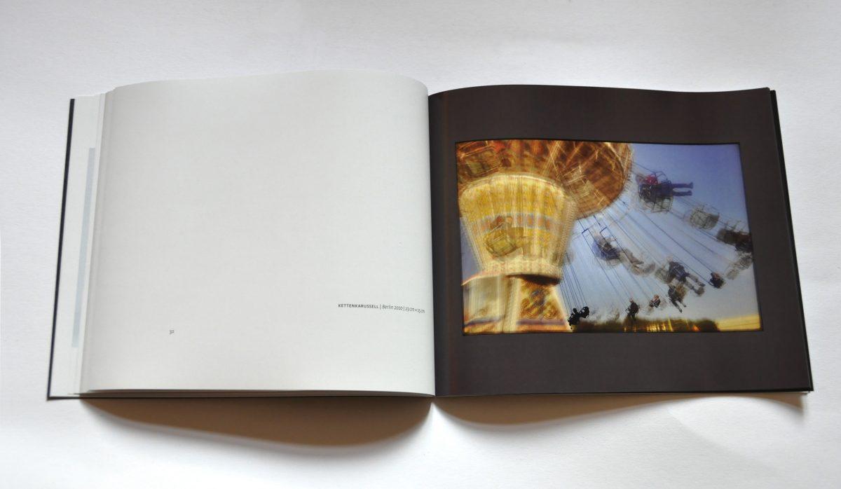 """Innenansicht des Ausstellungskataltogs """"3 Sekunden Gegenwart. Tempografien"""" in der Galerie F92, Berlin. Doppelseite mit mittlerem Bild, das ein Kettenkarussell zeigt"""