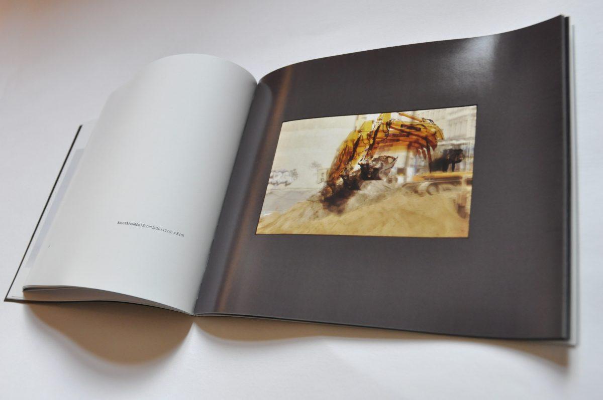 """Innenansicht des Ausstellungskataltogs """"3 Sekunden Gegenwart. Tempografien"""" in der Galerie F92, Berlin. Doppelseite mit kleinem Bild, das einen Bagger zeigt"""