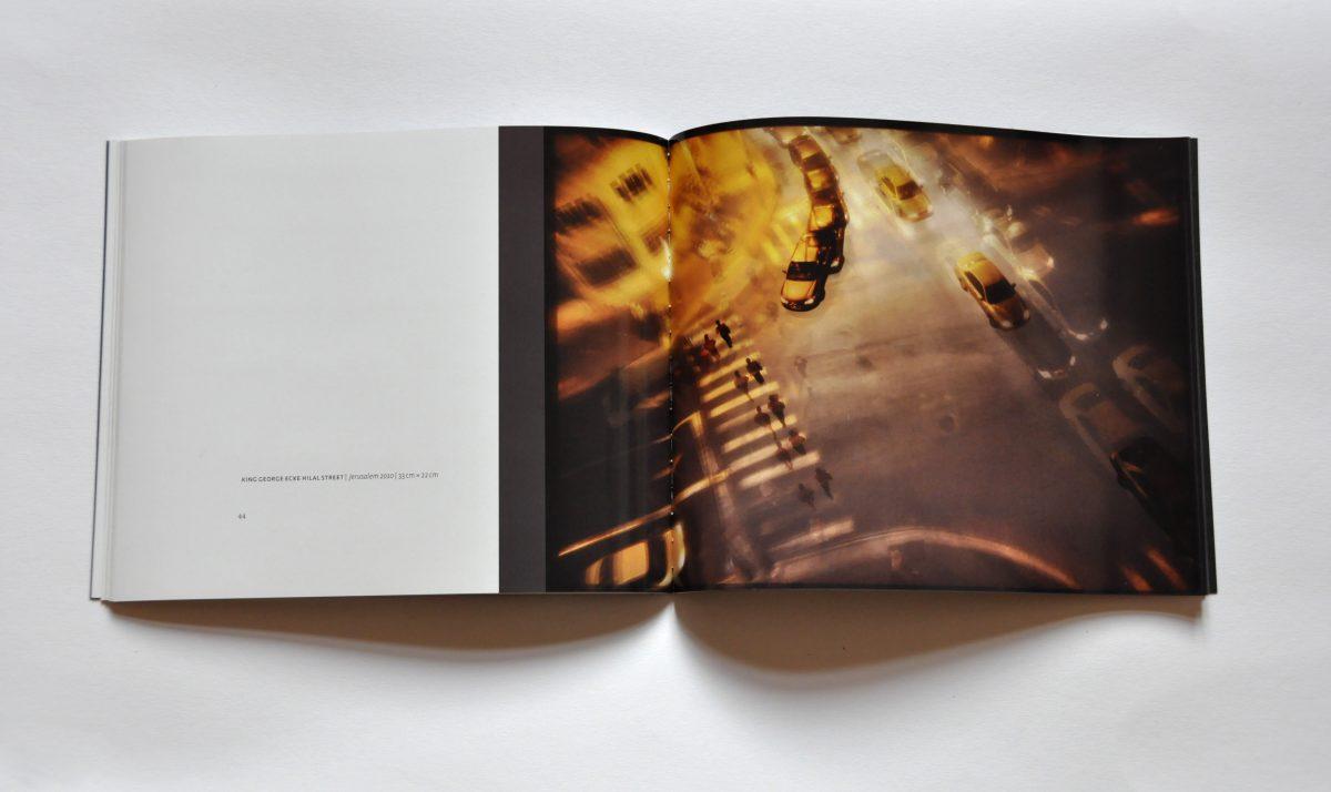 """Innenansicht des Ausstellungskataltogs """"3 Sekunden Gegenwart. Tempografien"""" in der Galerie F92, Berlin. Doppelseite mit großem Bild, das eine Straße im Dunkeln von oben zeigt"""