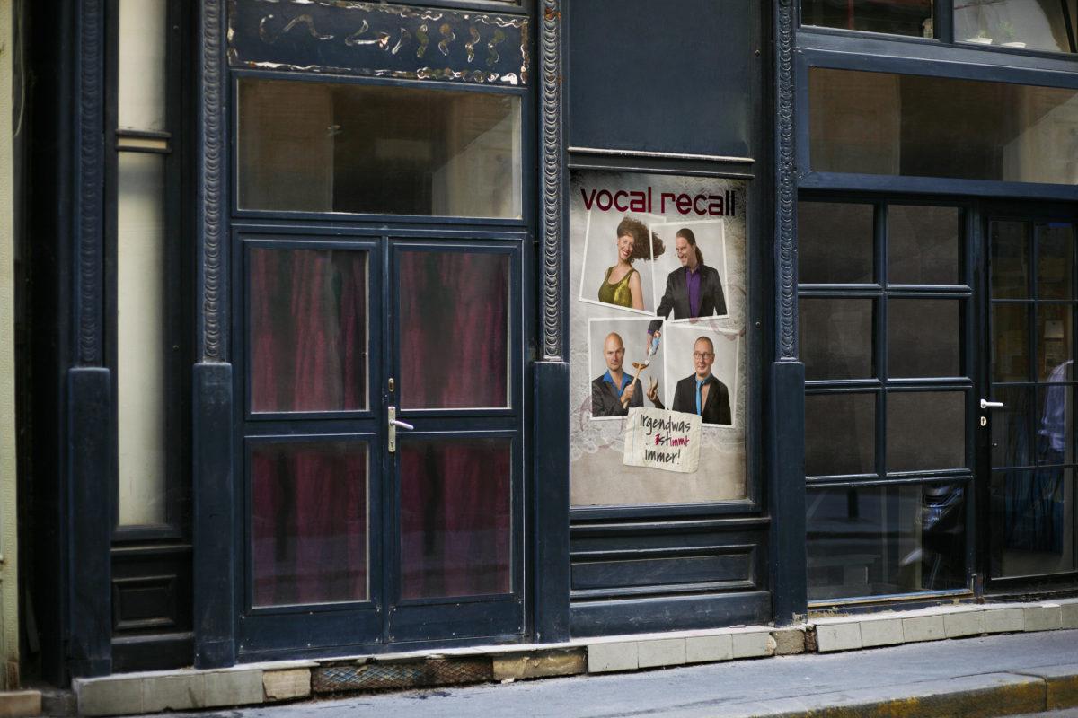 Ansicht des plakatierten Posters im Schaufenster, Portraits der vier Musiker von Vocal Recall auf Tischdecke mit Zettel und Weinglasflecken, Berliner Kabarett-Band